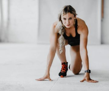 Body care in middle age and start workout at home or gym. Confident mature lady athlete or trainer in sportswear and fitness tracker ready to run in gym or home interior in morning, free space